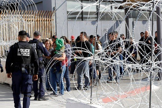 In this Nov. 19, 2018, file photo, people line up to cross into the United States from Tijuana, Mexico, seen through barriers topped with concertina wire at the San Ysidro port of entry in San Diego.  (AP Photo/Gregory Bull, file)