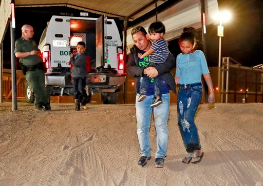 FILE - In this July 18, 2018 file photo, a Honduran man carries his 3-year-old son as his daughter and other son follow to a transport vehicle after being detained by U.S. Customs and Border Patrol agents in San Luis, Ariz. (AP Photo/Matt York, File)