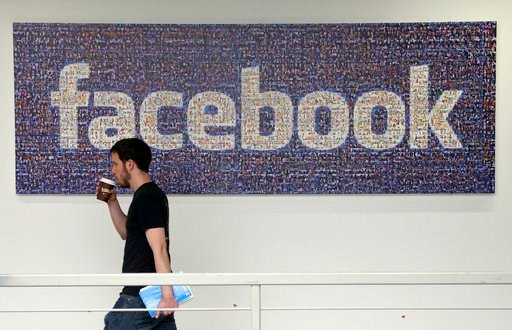 (AP Photo/Jeff Chiu, File) FILE - In this March 15, 2013, file photo, a man walks past a sign at Facebook headquarters in Menlo Park, California, USA.
