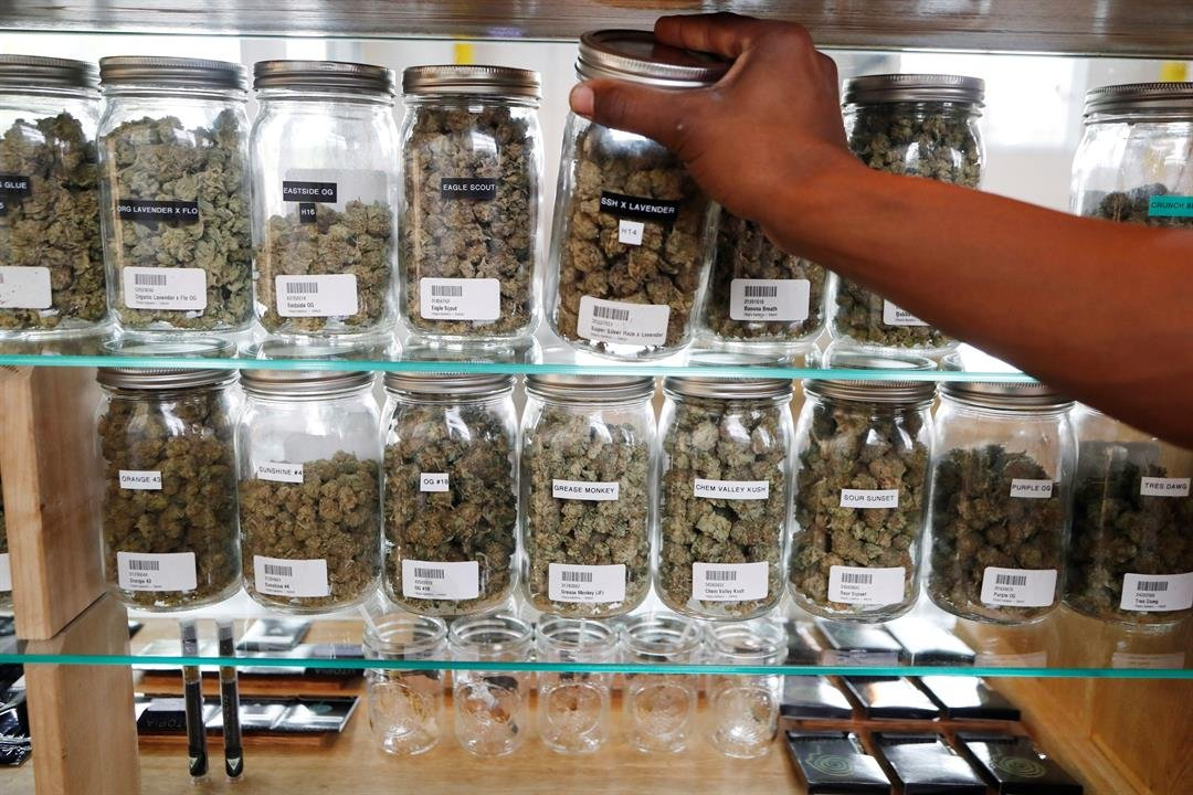 In this Oct. 2, 2018, file photo, a clerk reaches for a container of marijuana buds for a customer at Utopia Gardens, a medical marijuana dispensary in Detroit.  (AP Photo/Carlos Osorio, File)