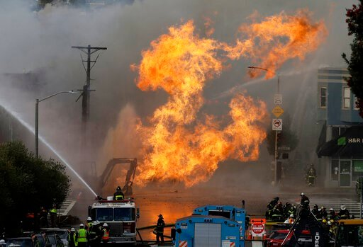 San Francisco firefighters battle a fire on Geary Boulevard in San Francisco, Wednesday, Feb. 6, 2019. Construction workers cut a natural gas line, San Francisco Fire Chief Joanne Hayes-White said. (AP Photo/Jeff Chiu)