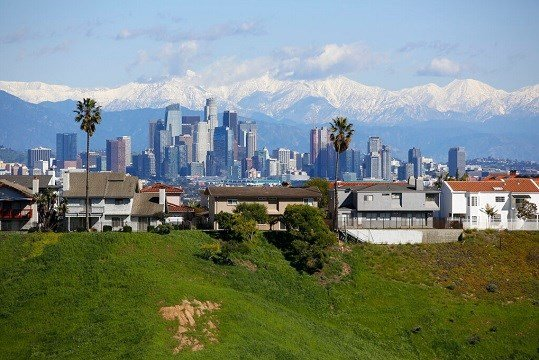 California's mountains glistening with snow are seen behind the Los Angeles skyline Wednesday, Feb. 6, 2019. (AP Photo/Damian Dovarganes)