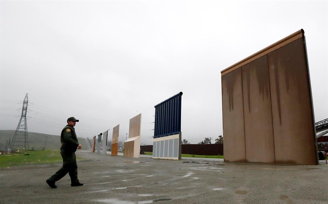 Border Patrol agent Vincent Pirro walks towards prototypes for a border wall Tuesday, Feb. 5, 2019, in San Diego. (AP Photo/Gregory Bull)