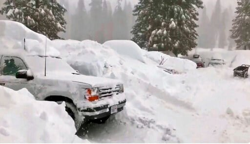 (Joel Keeler via AP) This Tuesday, Feb. 5, 2019 photo from video by Joel Keeler shows vehicles buried in the parking lot of the snowed-in Montecito Sequoia Lodge in Kings Canyon National Park in California's Sierra Nevada.