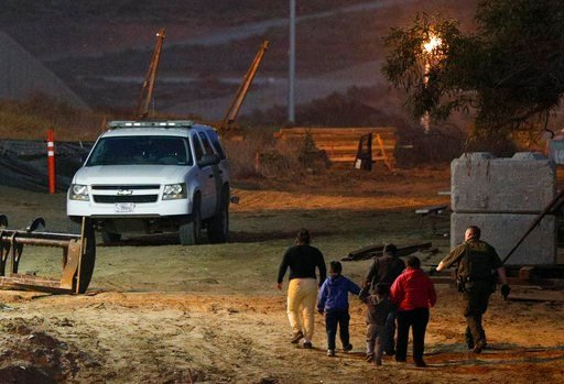 Migrants are escorted by a U.S. Border Patrol agent as they are detained after climbing over the border wall from Playas de Tijuana, Mexico, to San Ysidro, Calif., Monday, Dec. 3, 2018. (AP Photo/Rebecca Blackwell)