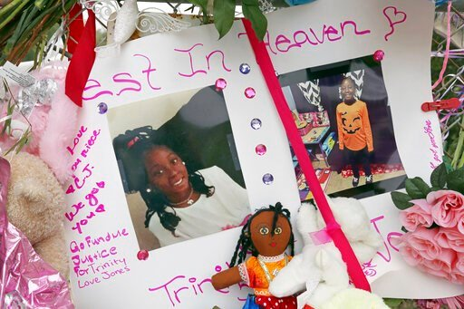 Photos adorn a large memorial to Trinity Love Jones, the 9-year-old girl whose body was found in a duffel bag along a suburban Los Angeles equestrian trail, in Hacienda Heights, Calif., Monday, March 11, 2019. Two people have been detained in connection w