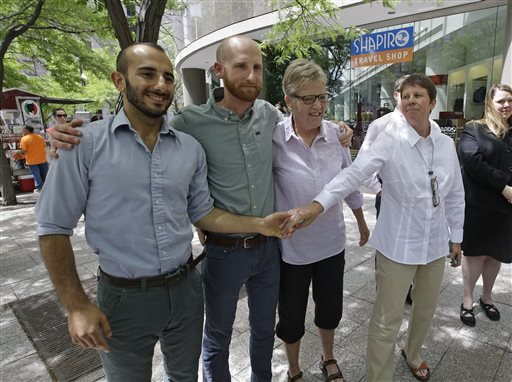 From left, plaintiffs Moudi Sbeity, Derek Kitchen, Laurie Wood and Kody Partridge, two of the three couples who brought the lawsuit against Utah's gay marriage ban, stand together at a news conference outside their lawyer's office in Salt Lake City. (AP)