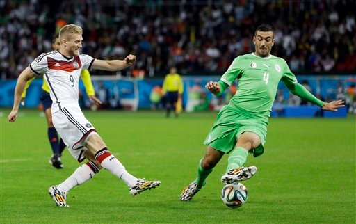 Germany's Andre Schuerrle, left, takes a shot past Germany's Benedikt Hoewedes during the World Cup round of 16 soccer match between Germany and Algeria at the Estadio Beira-Rio in Porto Alegre, Brazil, Monday, June 30, 2014. (AP Photo/Kirsty Wigglesworth