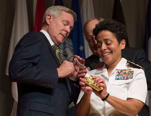 In a Photo provided by the U.S. Navy, Adm. Michelle Howard, right, lends a hand to Secretary of the Navy Ray Mabus as he and Wayne Cowles, Howard's husband, put four-star shoulder boards on Howard's service white uniform. (AP)
