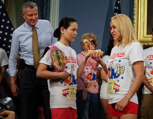 New York City Mayor Bill de Blasio watches hot dog eating contestants Sonya Thomas, left, and Miki Sudo, right, during a news conference to promote the upcoming Nathan's Famous Fourth of July Hot-Dog Eating Contest tomorrow Thursday, July 3, 2014. (AP)